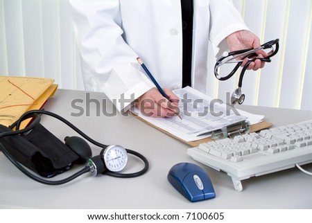 A woman holding a stethoscope; standing by a desk with a blood pressure cuff laying on it. - stock photo