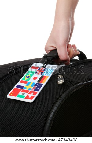 A woman holding a suitcase with global international flags - stock photo