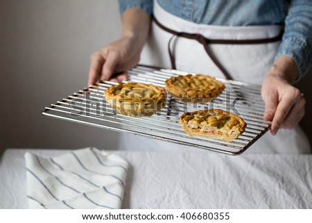 a woman holding a tray with fresh baked mozzarella cheese and cherry tomatoes pie with a lattice crust