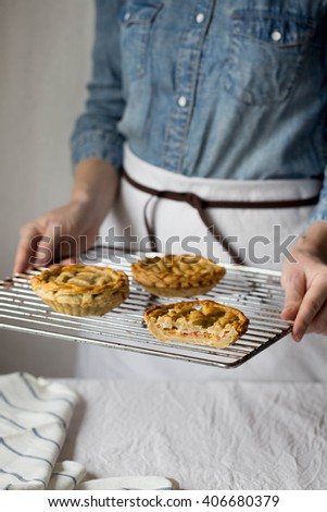 a woman holding a tray with fresh baked mozzarella cheese and cherry tomatoes pie with a lattice crust - stock photo