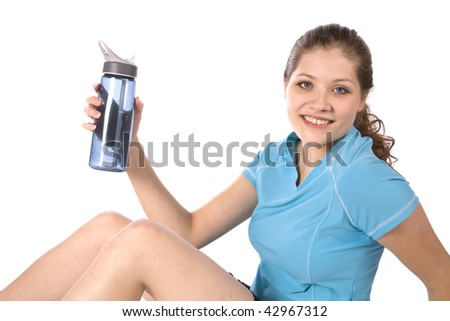 A woman holding a water bottle after exercising with a happy expression on her face. - stock photo