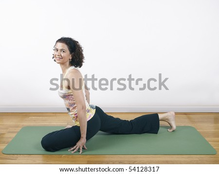 A woman holding a yoga pose on a floor mat