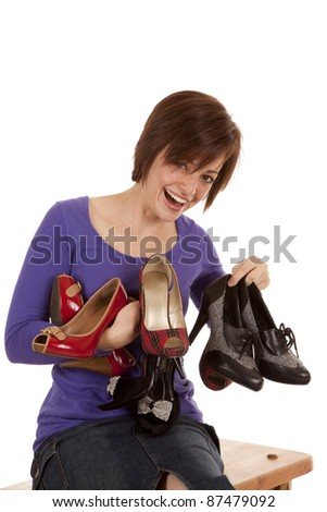 A woman holding an arm full of shoes with a happy expression on her face.