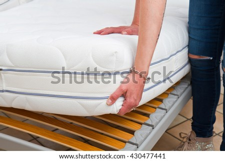 A woman  holding demonstrations quality mattress in the bedroom