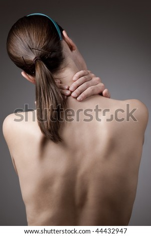 A woman holding her neck in pain with bare back - stock photo