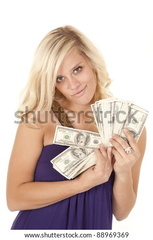 A woman holding on to a handful of money with a small smile on her face. - stock photo