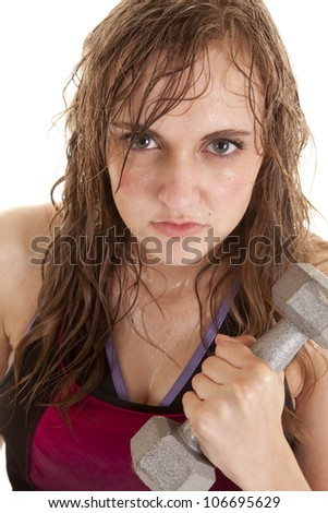 A woman holding on to a weight with sweat running down her face with a serious expression on her face. - stock photo