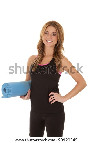 A woman holding on to an exercise mat with  a smile on her face. - stock photo