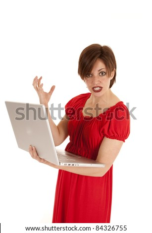 a woman holding on to her computer with an angry expression on her face. - stock photo