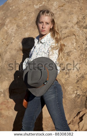 a woman holding on to her cowgirl hat with a serious expression on her face. - stock photo