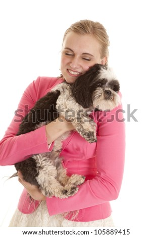 A woman holding on to her dog with a smile on her face. - stock photo