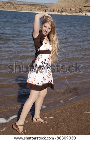 A woman holding on to her hair walking down the beach. - stock photo