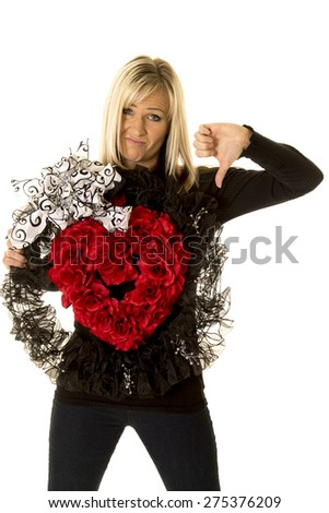 A woman holding on to her heart wreath with her thumb pointing down. - stock photo