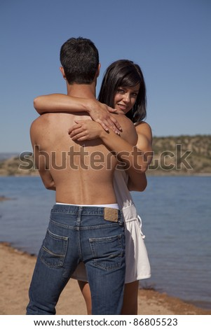 A woman holding on to her man while they are standing on the beach. - stock photo