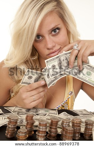 A woman holding on to her money counting all the money she has with a serious expression on her face. - stock photo
