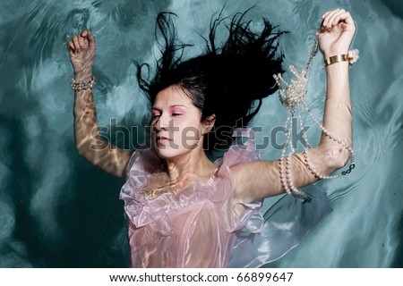 A woman holding on to her pearl necklace and in her pink dress floating on top of the water. - stock photo