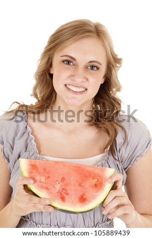 A woman holding on to her piece of watermelon with  a smile on her face. - stock photo