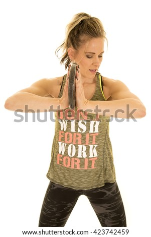A woman holding on to her weight working on her chest muscles. - stock photo