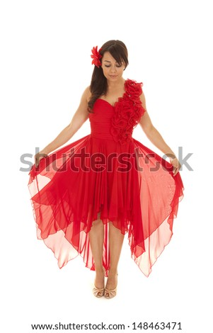 a woman holding out her red dress looking down. - stock photo
