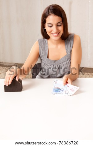 A woman holding out money (euro) in exchange for a house - stock photo