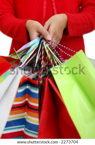 A woman holding several colorful shopping bags - stock photo