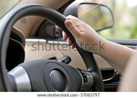 A woman holding the steering wheel of a car with one hand while driving. - stock photo
