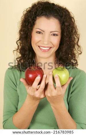A woman holding two apples.