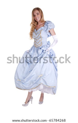 a woman holding up her princess dress showing off her shoes, with a smile on her face. - stock photo