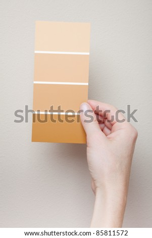 A woman holds a card with four paint swatches near a wall for comparison. - stock photo
