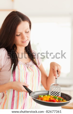 A woman holds a frying pan with vegetables in it
