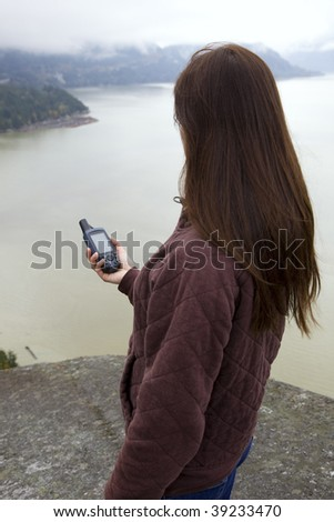 A woman holds a GPS as she tries to find her way. - stock photo