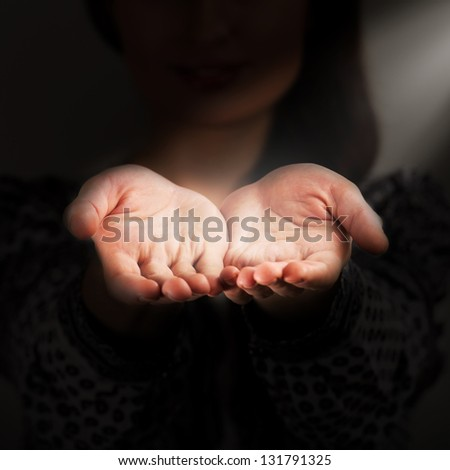 A woman holds a handful, hands together, asks - stock photo