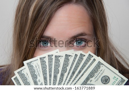 A woman holds a handful of cash to spend - stock photo