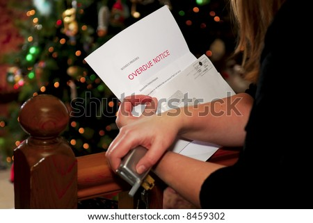 A woman holds an overdue Christmas bill, Christmas tree in background. - stock photo