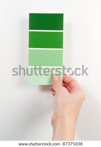 A woman holds green paint swatches near a white wall. - stock photo