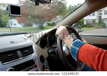 A woman holds the steering wheel of a car while driving down the road. - stock photo