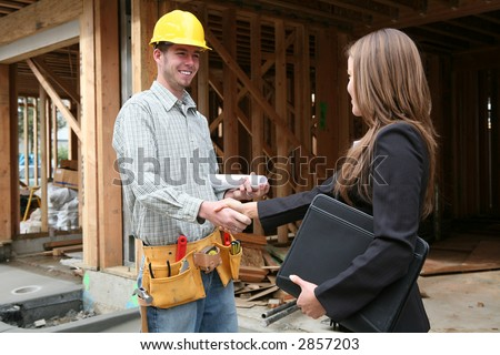 A woman home owner shaking hands with the construction worker - stock photo