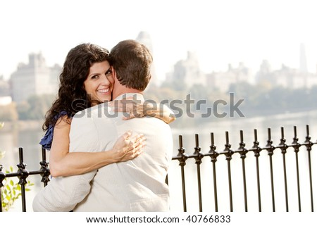 A woman hugging a man and looking at the camera with a smile - stock photo