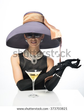 A woman in a big hat and sunglasses, like a movie star, drinking martinis - stock photo