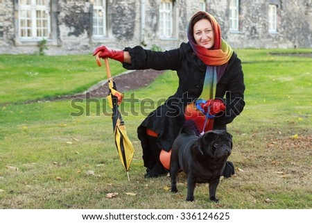 A woman in a black coat and a bright scarf on her head, on a walk in the autumn park , selective focus  - stock photo