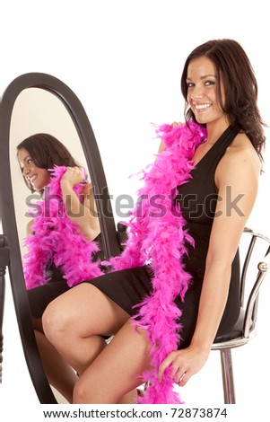 A woman in a black dress and a pink boa is sitting by a mirror. - stock photo