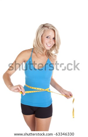A woman in a blue top is measuring her waist. - stock photo