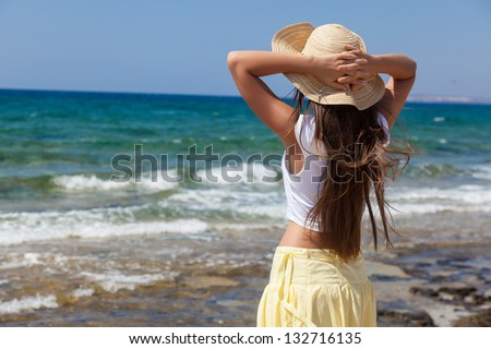 a woman in a bonnet is looking at the sea - stock photo