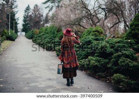 A woman in a burgundy hat and plaid winter coat in the avenue cold foggy park with suitcase like American flag Stars and Stripes, English vintage, look from the back - stock photo
