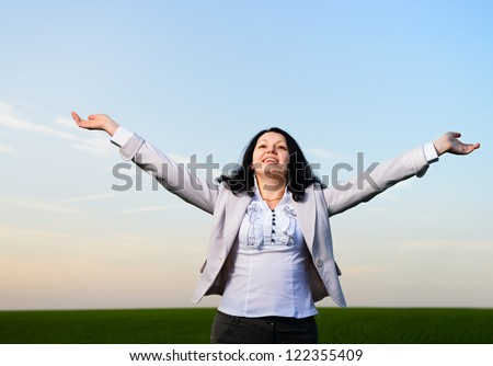 A woman in a business suit with their hands raised . On the background of the picturesque sky - stock photo