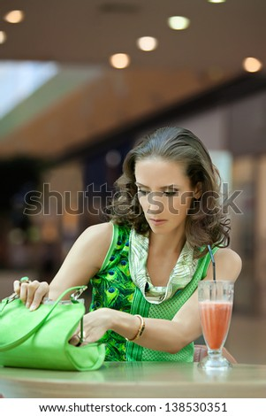 A woman in a cafe looking for something in her purse sitting at the table - stock photo