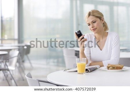A woman in a cafe or office canteen, texting on mobile phone - stock photo