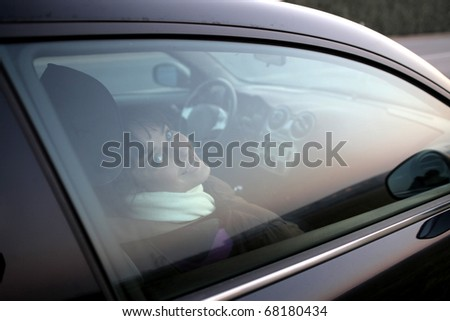 A woman in a car is  beaming through the window