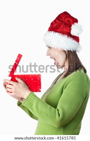 A woman in a Christmas scenario opening a gift with obvious delight on white