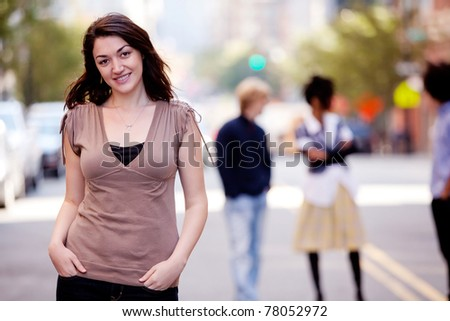 A woman in a city setting with friends in the background - stock photo